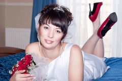Beautiful bride on the wedding blue bed Royalty Free Stock Photo