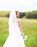 Beautiful bride with wedding bouquet of flowers outdoors in  field Stock Photos