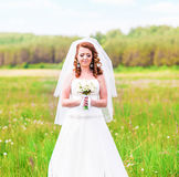 Beautiful bride with wedding bouquet of flowers outdoors in  field Stock Photo
