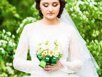 Beautiful bride with wedding bouquet of flowers outdoors in spring  park. Royalty Free Stock Photos