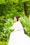 Beautiful bride with wedding bouquet of flowers outdoors in spring  park. Stock Image