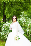 Beautiful bride with wedding bouquet of flowers outdoors in spring  park. Royalty Free Stock Photography