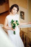 Beautiful bride with wedding bouquet of goes up the stairs, indoors. Royalty Free Stock Photo