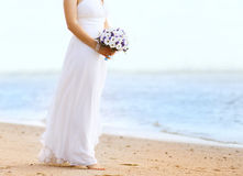 Beautiful bride with wedding bouquet outdoors. On the coast sea Stock Images
