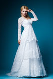 Beautiful bride in wedding dress on blue Stock Image