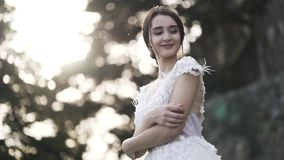 Beautiful bride in wedding dress on blurred background of bright sky and green tree leaves, marriage concept. Action. A. Beautiful bride in wedding dress on stock video footage