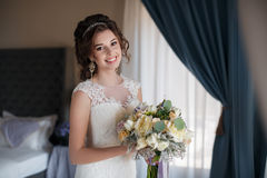 Beautiful bride in wedding dress with bouquet of flowers Stock Image