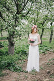 Beautiful bride in a wedding dress with bouquet and roses wreath posing in a green garden Stock Image