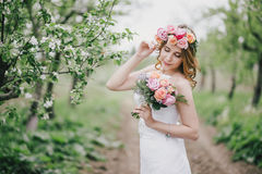 Beautiful bride in a wedding dress with bouquet and roses wreath posing in a green garden Royalty Free Stock Photography