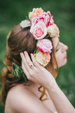 Beautiful bride in a wedding dress with bouquet and roses wreath posing in a green garden Stock Images