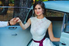 Beautiful bride in wedding dress comes out of car. royalty free stock image