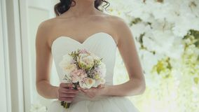 Beautiful bride in wedding dress with flowers in a studio. Close up Stock Image