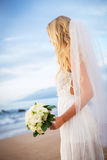 Beautiful bride in wedding dress with flowers at sunset on beaut Stock Photos