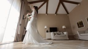 Beautiful bride in the wedding dress going to the window in the hotel room stock video footage