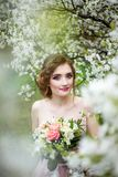 Beautiful bride in wedding dress holding bouquet in hands stock photography