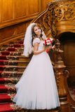 Beautiful bride in wedding dress holding a cute bouquet with red and white roses posing on background of vintage wooden. Interior Stock Photos