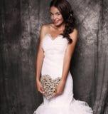 Beautiful bride in wedding dress holding decorative heart Stock Photo