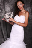 Beautiful bride in wedding dress holding decorative heart Stock Photo