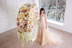 Beautiful bride in wedding dress in the interior. Beautiful bride in a wedding dress in an interior with a hanging circle in floral arrangements on a window Royalty Free Stock Photos