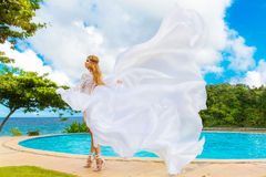 Beautiful bride in wedding dress with long train standing at the. Infinity pool in the hotel on a tropical island. Wedding and honeymoon Stock Image