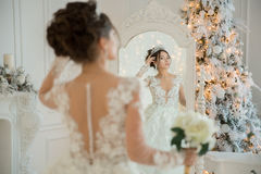 Beautiful bride in a wedding dress at a mirror in Christmas. Gir Royalty Free Stock Photos