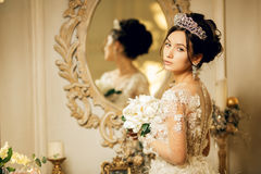 Beautiful bride in a wedding dress at a mirror in Christmas. Gir Royalty Free Stock Image