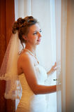 Beautiful bride in wedding dress near window Stock Images