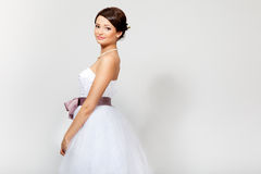 Beautiful bride in wedding dress. Portrait of a beautiful brunette bride in white wedding dress with lilac bow, in studio, looking at camera Stock Image