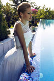 Beautiful bride in wedding dress posing beside a swimming pool Stock Images