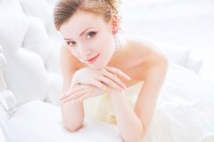 Beautiful bride in wedding dress. The bride sits on a antique chair with a bouquet in a wedding dress indoor Stock Photos