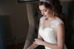 Beautiful bride in wedding dress sitting in a chair in the hotel room Royalty Free Stock Images