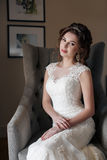 Beautiful bride in wedding dress sitting in a chair in the hotel room Stock Photo