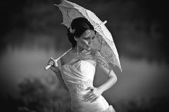 Beautiful bride in wedding dress with umbrella, outdoors portrait. Black and white Stock Image