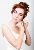 Beautiful bride in a wedding dress with a wedding makeup and hairstyle. Bride inserts earrings in her ear Stock Photos