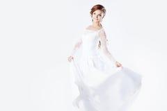 Beautiful bride in wedding dress, white background. Beautiful smiling woman in a wedding dress Royalty Free Stock Photo