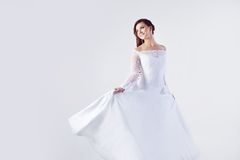 Beautiful bride in wedding dress, white background. Beautiful smiling woman in a wedding dress Royalty Free Stock Images