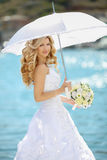 Beautiful bride in wedding dress with white umbrella and bouquet Royalty Free Stock Images