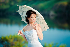 Beautiful bride in wedding dress with white umbrella, outdoors portrait Stock Image