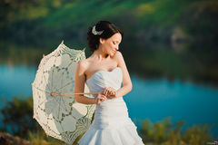 Beautiful bride in wedding dress with white umbrella, outdoors portrait.  Royalty Free Stock Photo