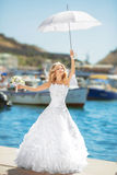 Beautiful bride in wedding dress with white umbrella posing over Stock Photos