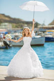 Beautiful bride in wedding dress with white umbrella posing over Royalty Free Stock Image