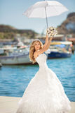 Beautiful bride in wedding dress with white umbrella posing over Stock Photo