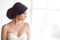 Beautiful bride. Wedding hairstyle make-up luxury fashion dress concept. Beauty portrait of bride wearing fashion wedding dress with feathers with luxury delight Royalty Free Stock Photography