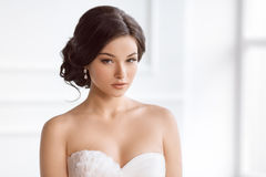 Beautiful bride. Wedding hairstyle make-up luxury fashion dress concept. Beauty portrait of bride wearing fashion wedding dress with feathers with luxury delight Stock Images