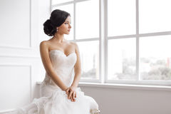Beautiful bride. Wedding hairstyle make-up luxury fashion dress concept. Bride in beautiful dress sitting on chair indoors in white studio interior like at home royalty free stock images