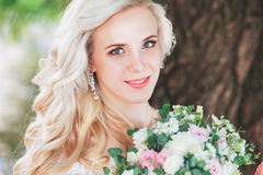 Beautiful bride. Wedding hairstyle and make up.Young bride in wedding dress holding bouquet Royalty Free Stock Images