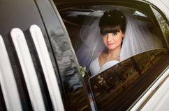 Beautiful bride in wedding limousine. Bride looks out of the white limousine window stock photos