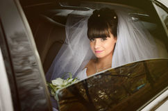 Beautiful bride in wedding limousine. Bride looks out of the white limousine window royalty free stock photo
