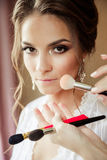 Beautiful bride wedding makeup and hair-style. Stylist makes makeup bride on wedding day. Stock Photos