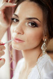 Beautiful bride wedding makeup and hair-style. Stylist makes makeup bride on wedding day. Stock Photography